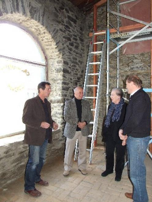 Studying restoration work on the roof of Olivers at Clyde are (from left) Butler Farm owner Nick...