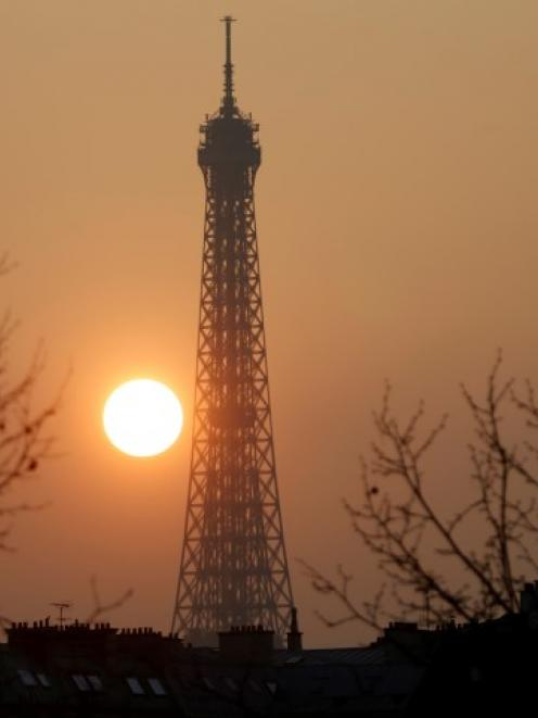 Sunset in Paris, which has been basking in a streak of unseasonable sunshine but also...