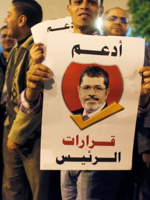 Supporters of Egypt's president Mohamed Mursi hold banners reading 'I support the President's...