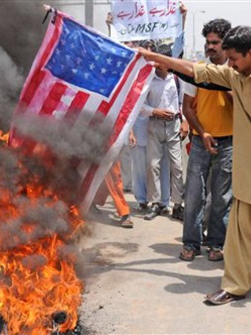 Supporters of Pakistan's Muslim League burn a representation of the US flag during a...