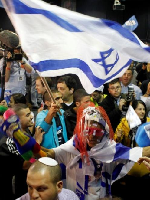 Supporters of Prime Minister Benjamin Netanyahu's Likud party celebrate after the exit polls were...