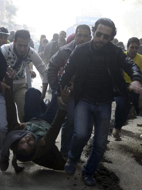 Supporters of the Muslim Brotherhood and ousted Egyptian President Mohamed Mursi carry an injured...