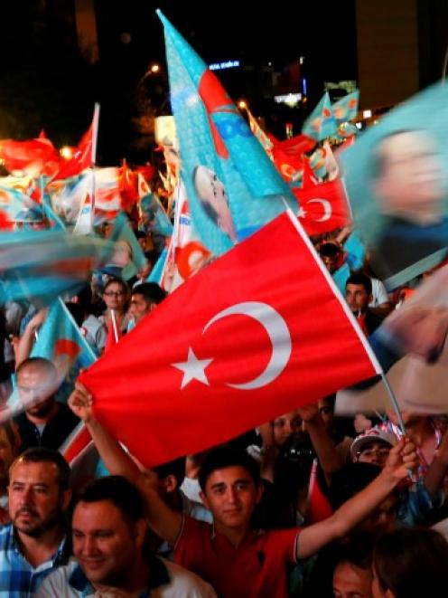 Supporters of Turkey's Prime Minister Tayyip Erdogan celebrate his election victory in front of...