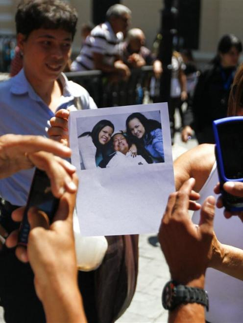 Supporters of Venezuelan President Hugo Chavez take pictures of a copy of a photograph of Chavez...