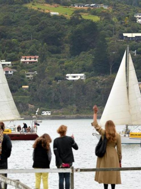 Supporters wave to SV Tiama (left) and Erewhon as the yachts sail past Ravensbourne on Saturday....