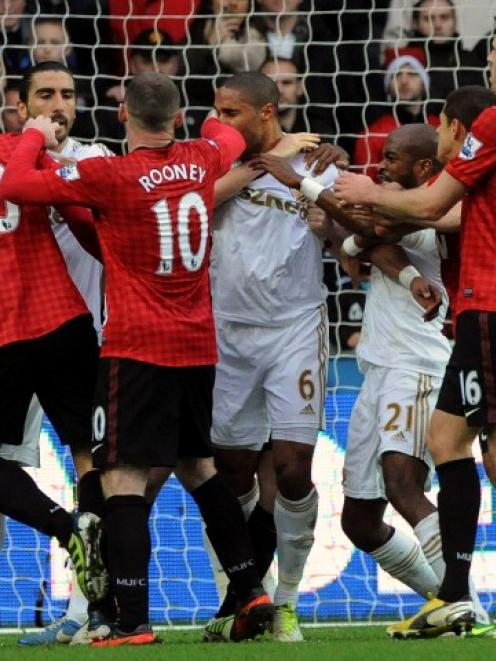 Swansea City and Manchester United players scuffle after a foul on Robin Van Persie (L) during...