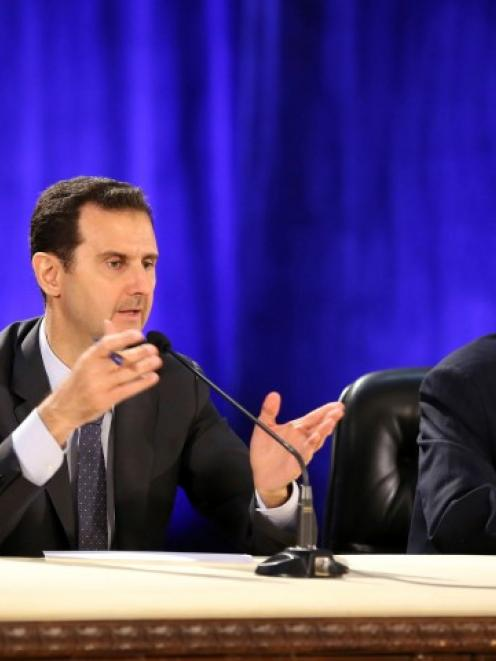 Syria's President Bashar al-Assad (L) meets professors and students of political science at a...