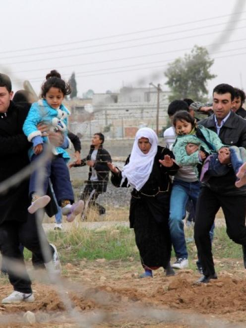Syrians run as they flee from the Syrian town of Ras al-Ain to Turkish border town of Ceylanpinar...