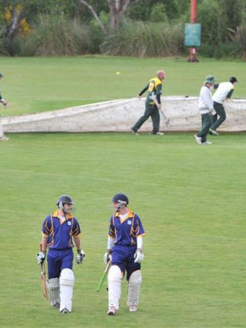Taieri batsmen Ash Simpson (left) and Toby Batchelor walk off the field as the covers go on at...