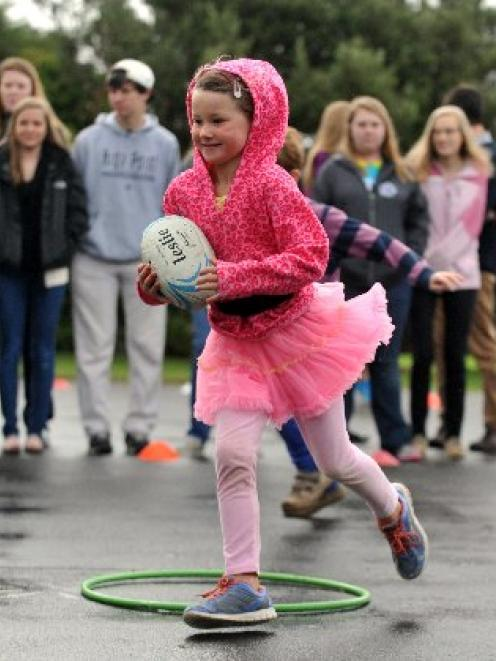 Taieri Beach School pupil Hannah Jaquiery (6) shows students from High Point University, North...