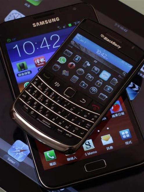The Blackberry Bold smartphone, Samsung Galaxy Note phablet and Apple iPad 2 tablet are displayed...