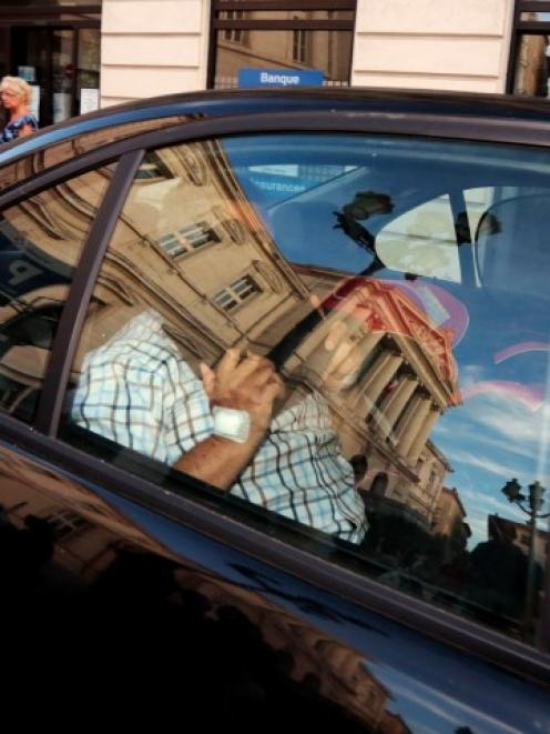 The courthouse in Nice is reflected in the car window as Stephan Turk leaves after being indicted...