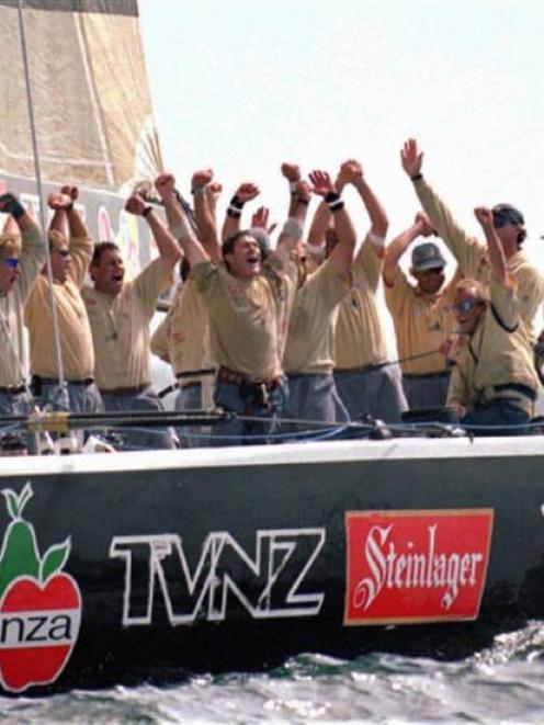 The crew members of New Zealand's Black Magic celebrate as they cross the finish line in the...