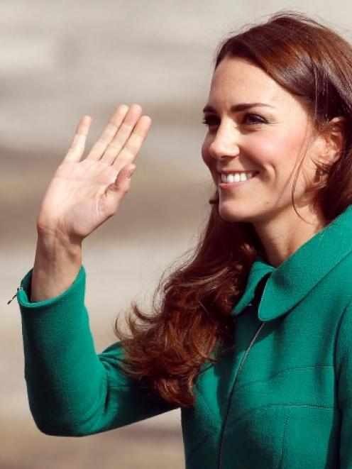 The Duchess of Cambridge waves after arriving with Prince William at Hamilton airport before...