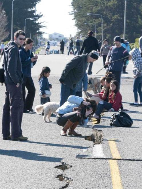 The earthquake-damaged roadway on the South Brighton bridge approach attracts the curious after...