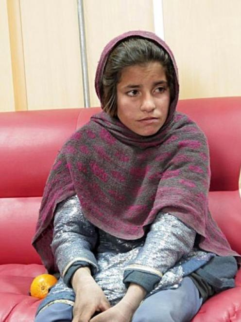 The girl who was caught wearing a suicide bomb vest sits at a police office in Helmand province...