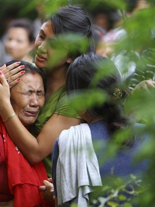 The mother (L) of flight attendant Ashmita Shrestha breaks down as she waits for the body of her...