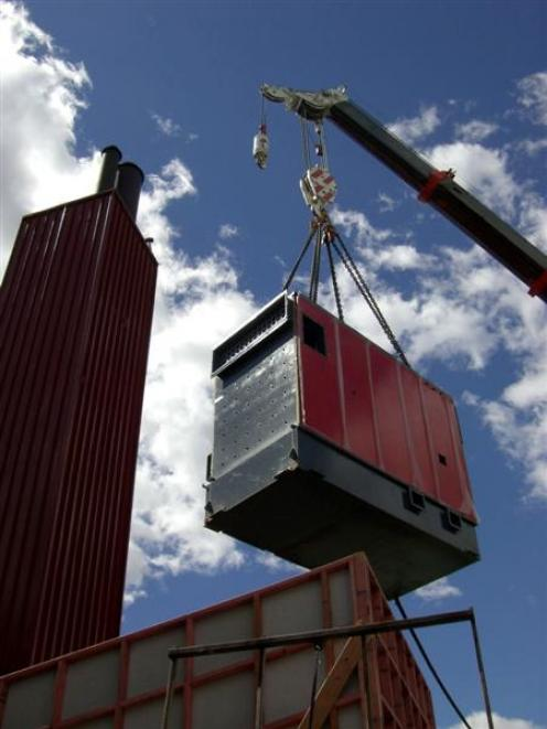 The new woodchip-fired boiler is carefully lifted into place at Dunstan High School next to the...