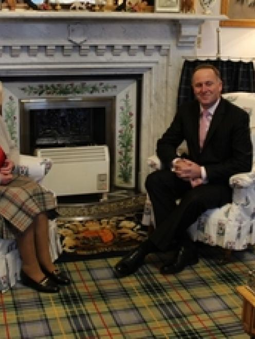The Queen, wearing a Balmoral tartan skirt and surrounded by family photos, meets Prime Minister...
