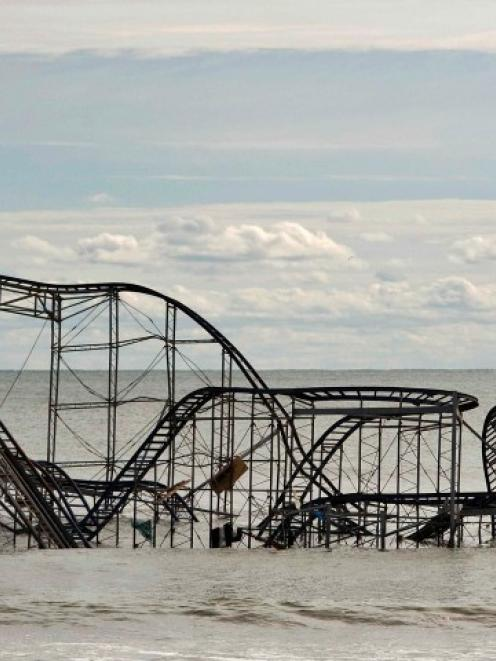 The remains of a roller coaster sit in the surf three days after Hurricane Sandy came ashore in...
