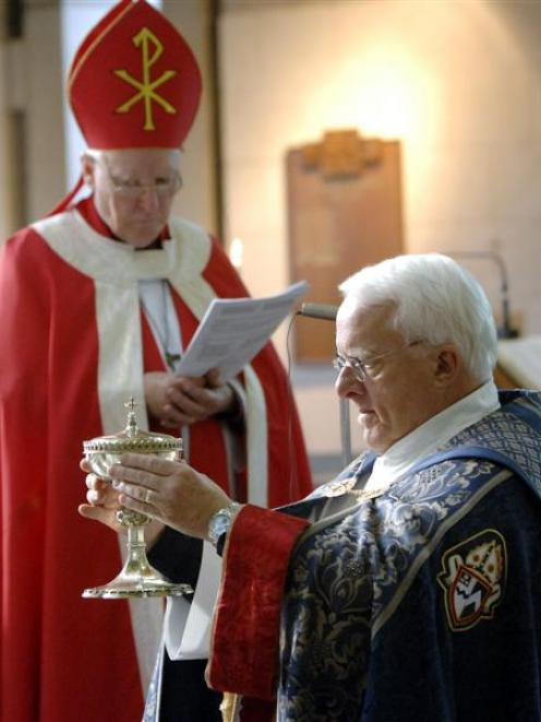 The Rev Dr Trevor James (right) receives a chalice as a symbol of ministry, watched by the...
