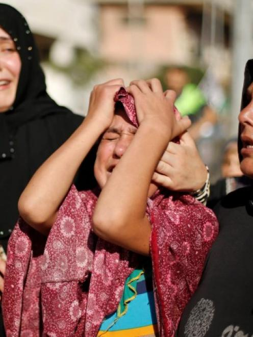 The sister (C) of a Palestinian boy who medics said was killed with three other children from the...