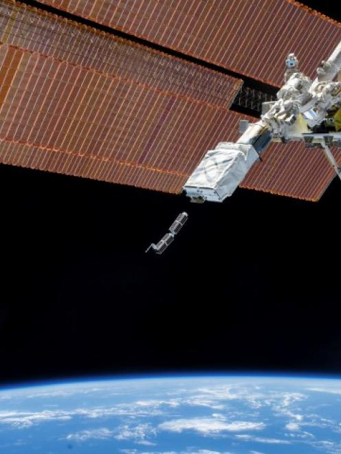 The Small Satellite Orbital Deployer, in the grasp of the Kibo laboratory robotic arm, is...