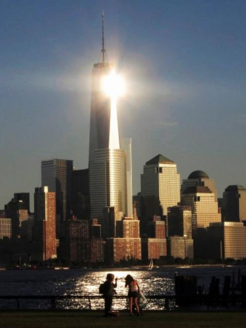 The sun reflects off New York's One World Trade Center as people stand in a park in Hoboken, New...