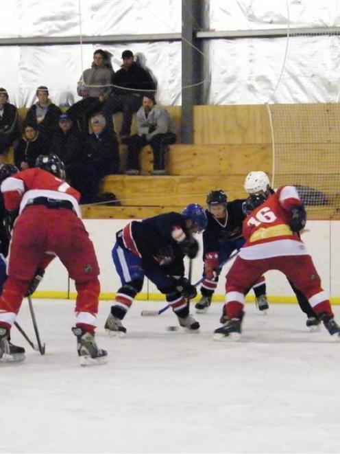 The Tekapo Bull Tahr players (in red, from left) Geoff Brooks and Bryan North face off against...