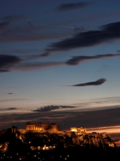 The temple of the Parthenon is illuminated at the Acropolis hill in Athens. REUTERS/John Kolesidis