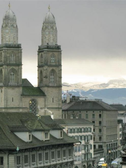 The twin towers of Grossmunster rise over Zurich, against the backdrop of the Swiss Alps. Photo...
