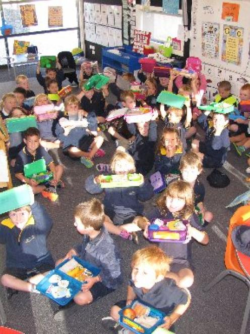 Three-quarters of this new entrants class at the Wanaka Primary School show their lunch boxes are...