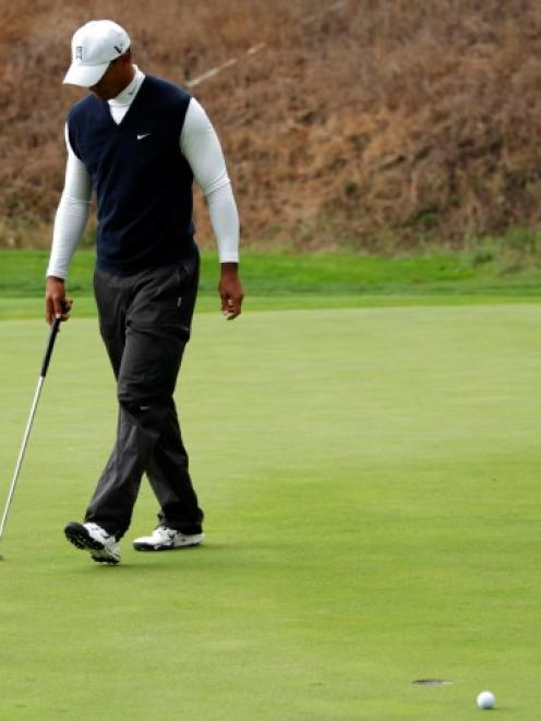 Tiger Woods reacts after missing a birdie putt at the 18th hole during the first round of the...