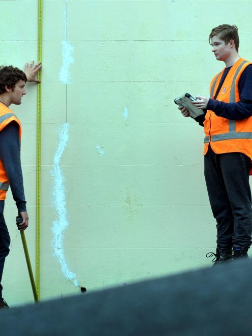 Tim Notman, left and Luke Kenneally assess a  Dunedin retaining wall. Photo by Peter Mcintosh