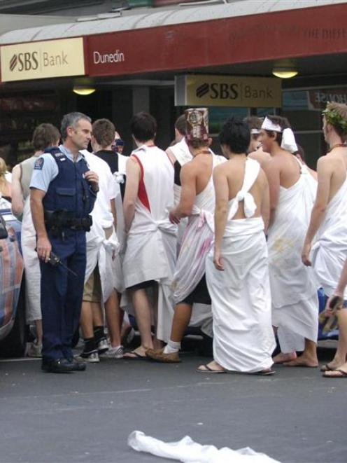 Police speak to students during February's toga parade, which descended into disorder, leaving...