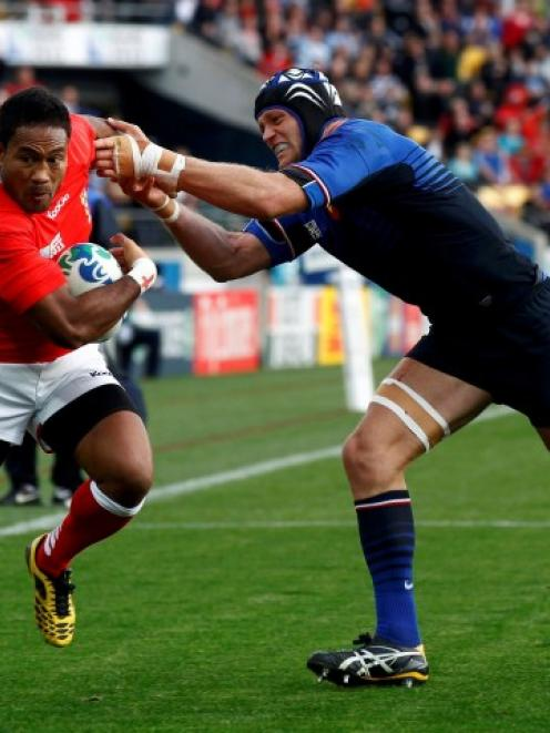 Tonga's Sukanaivalu Hufanga (L) shakes off France's Julien Bonnaire as he goes on to score a try...