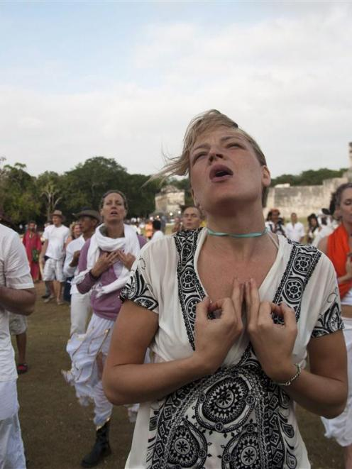 Tourists meditate at the archaeological zone of Chichen Itza in Mexico where thousands of mystics...