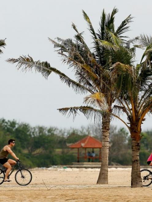Tourists ride along Bali's Nusa Dua Beach. Photo Getty
