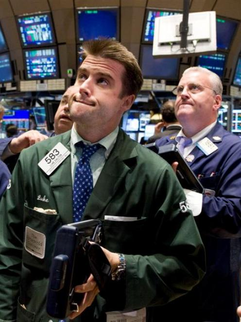 Trader Luke Dalton, foreground, watches the numbers from the floor of the New York Stock Exchange...