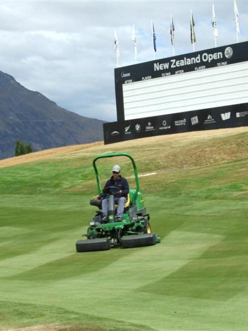 Trainee green keeper Mark Shuttleworth cuts the approach to the 18th green yesterday at The Hills...