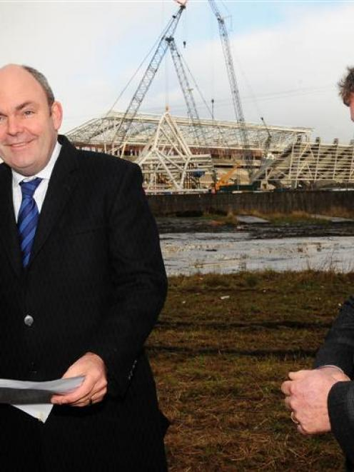 Transport Minister Steven Joyce (centre) checks the site of a planned roundabout, to be built as...