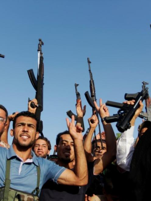 Tribal fighters shout slogans while holding weapons in Basra, southeast of Baghdad. REUTERS/...