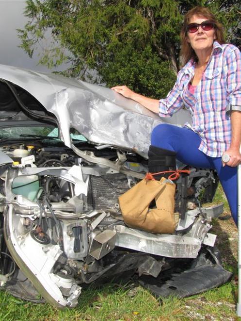 Trisha Nolan (53) of Okuru, South Westland, with her damaged car and damaged feet. Photo by Mark...