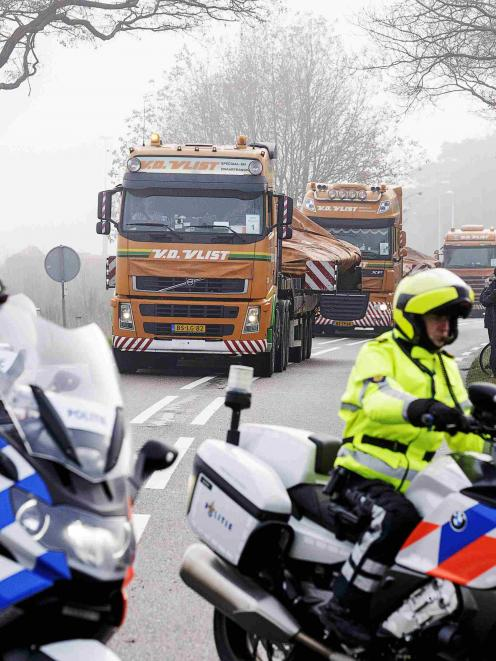 Trucks carrying wreckage from Malaysia Airlines flight MH17 arrive at a Dutch airforce base in...