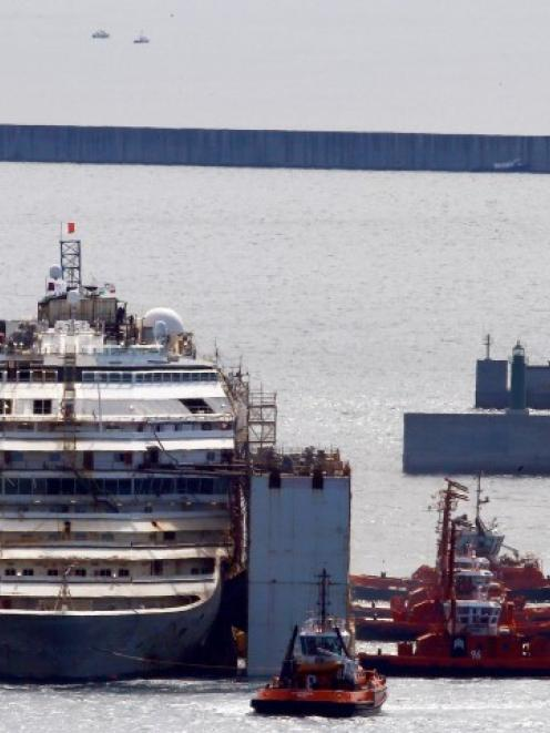 Tug boats push the Costa Concordia inside Genoa's port, in northern Italy, where the ship will be...