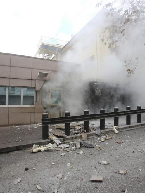 Turkish police officers react after an explosion at the entrance of the US Embassy in Ankara....