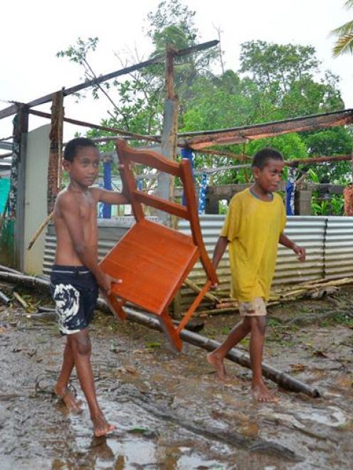 Twins Joen Soro and Mosikula Taitulo help remove the church furniture after the roof of Vusuya...