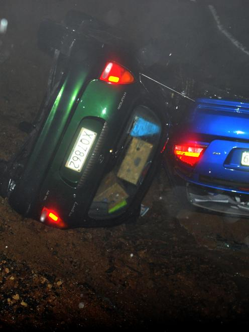 Two cars in a ditch after part of Highcliff Rd was swept away from in front of them last night....