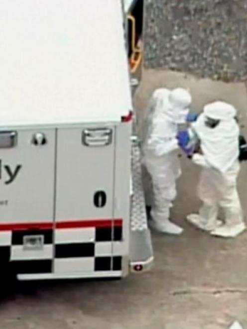 Two men in protective clothing exit an ambulance outside Emory University hospital in Atlanta,...