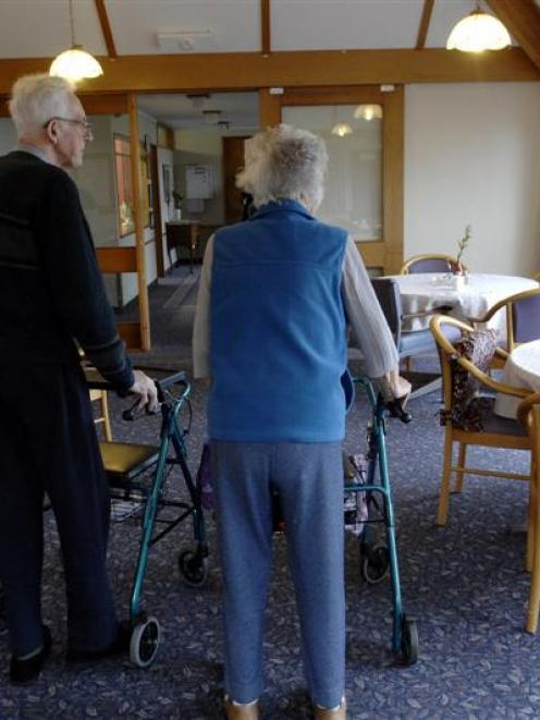 Two residents of Redroofs rest-home walk through the dining room. Photo by Linda Robertson.